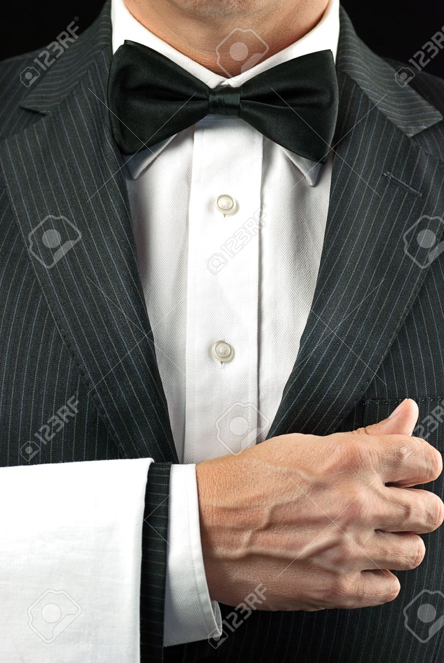 Close-up torso shot of a fine dining waiter in a bowtie and tux with a white pressed napkin over his arm - 15896354