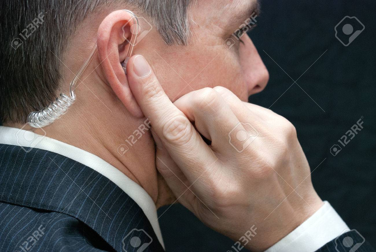Close-up of a secret service agent listening to his earpiece, close side. - 25307687