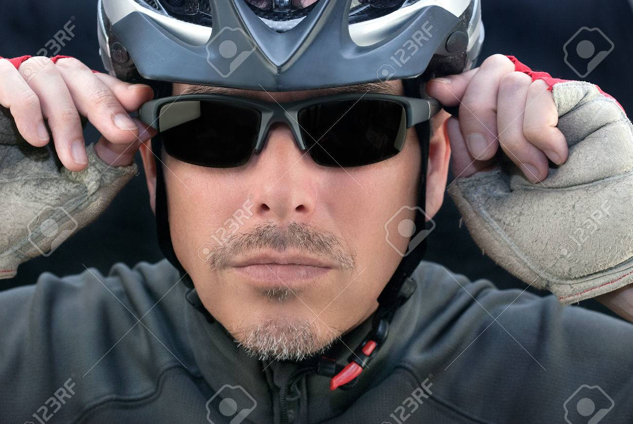 Close-up of bicycle courier putting on his sunglasses - 29349991