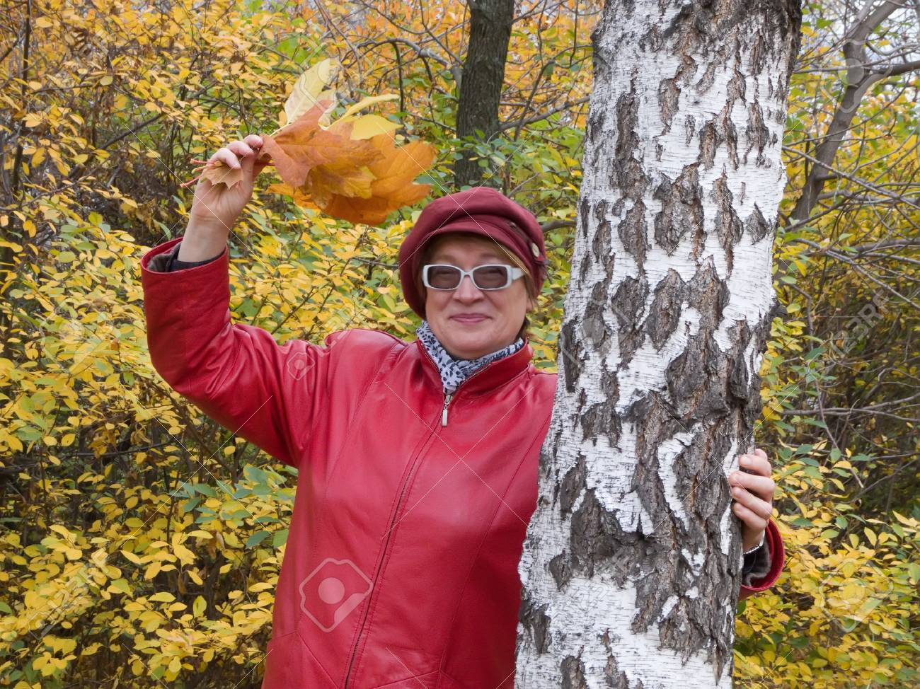 Smiling old lady in red stays in autumn park. Stock Photo - 3825543