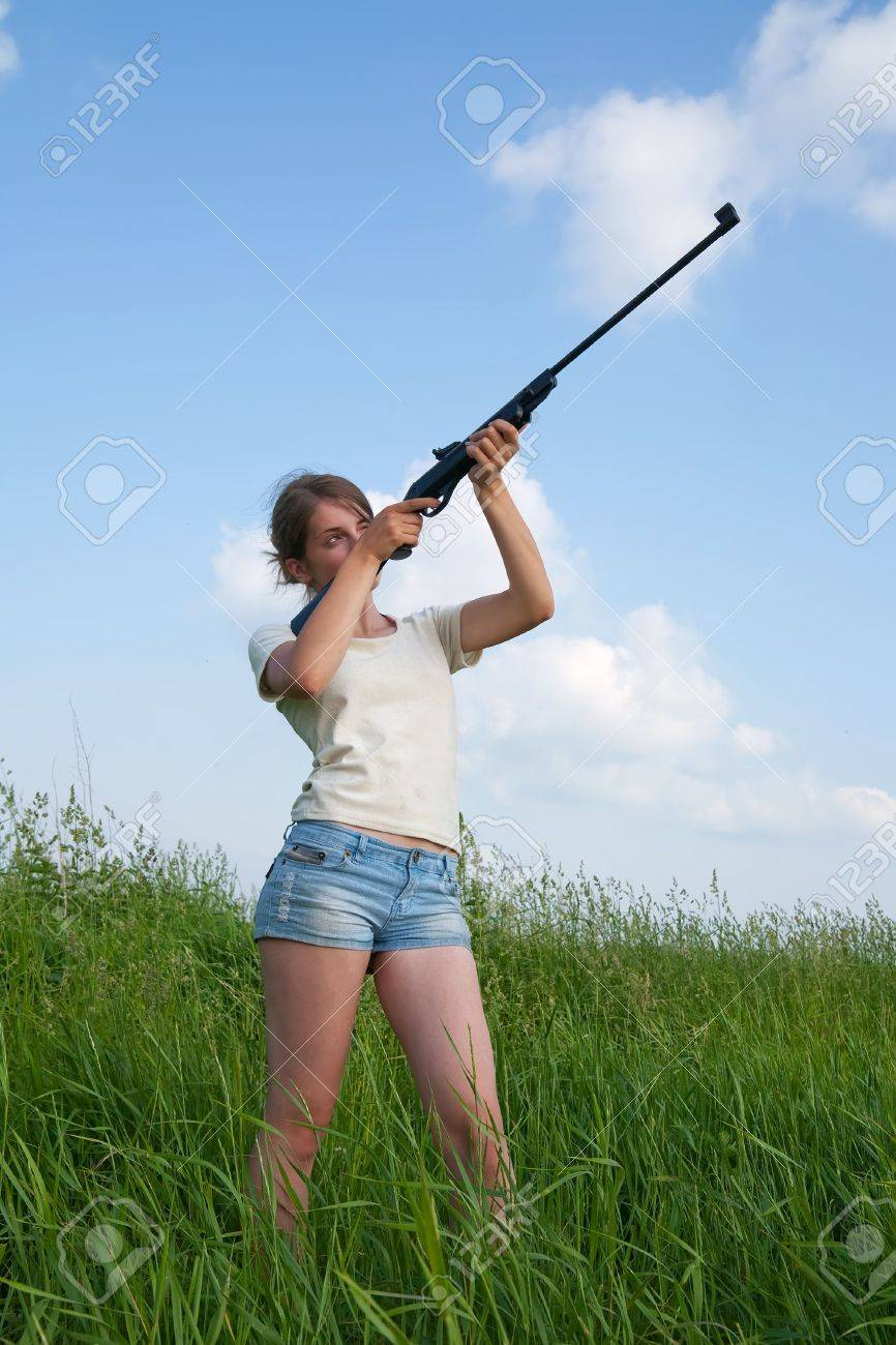 young woman aiming a pneumatic air rifle - 5177453
