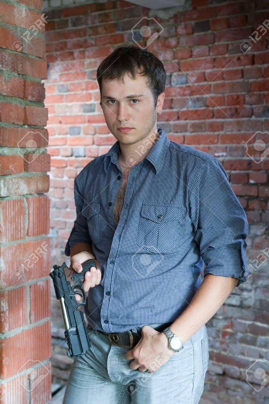 man in blue shirt  standing on brick background holding gun Stock Photo - 5654130