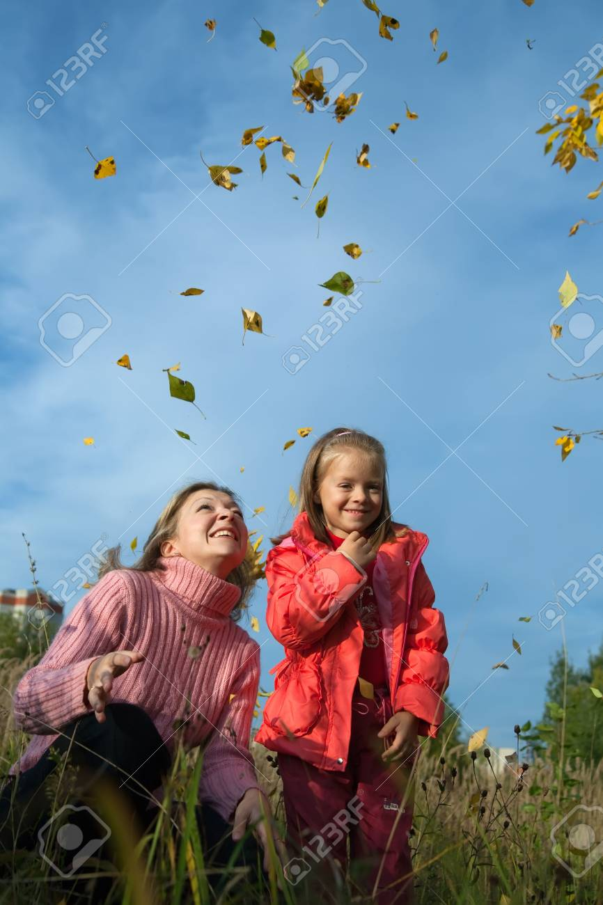 mother and her child throwing yellow maple leaves in the air in park Stock Photo - 5771629