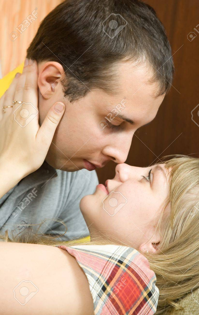 Young couple in love laying on the couch kissing Stock Photo - 7337765