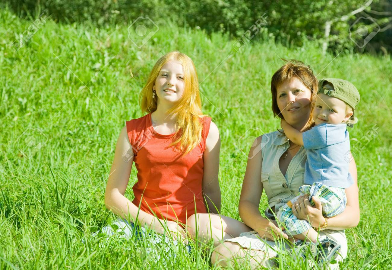Mother with children  sitting on the green grass Stock Photo - 7375331