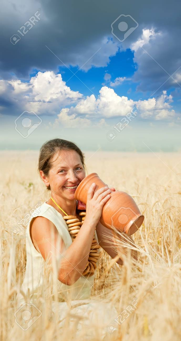 Woman in traditional clothes with jug at cereals field Stock Photo - 7465046