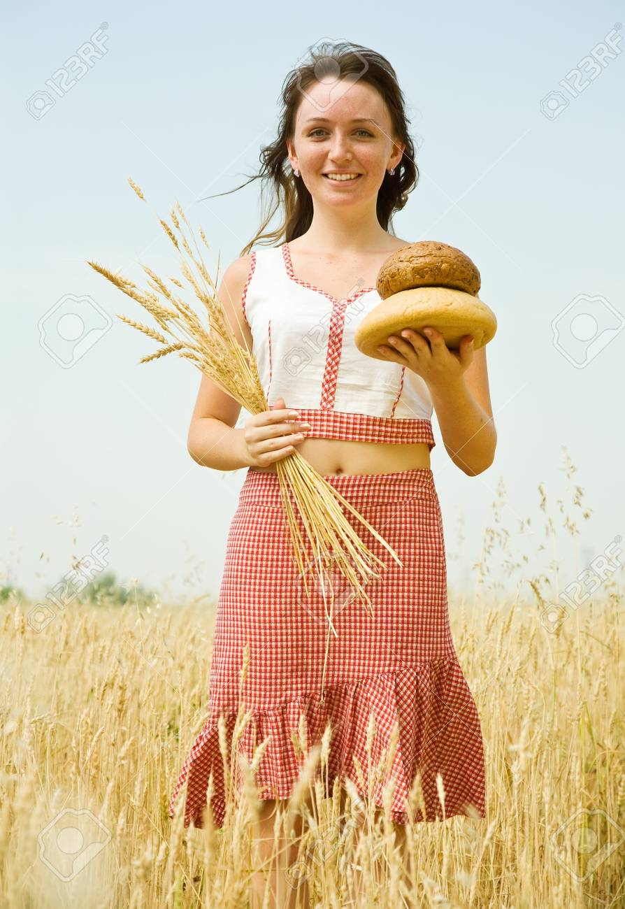Girl in traditional clothes with bread  at wheat field Stock Photo - 7529179