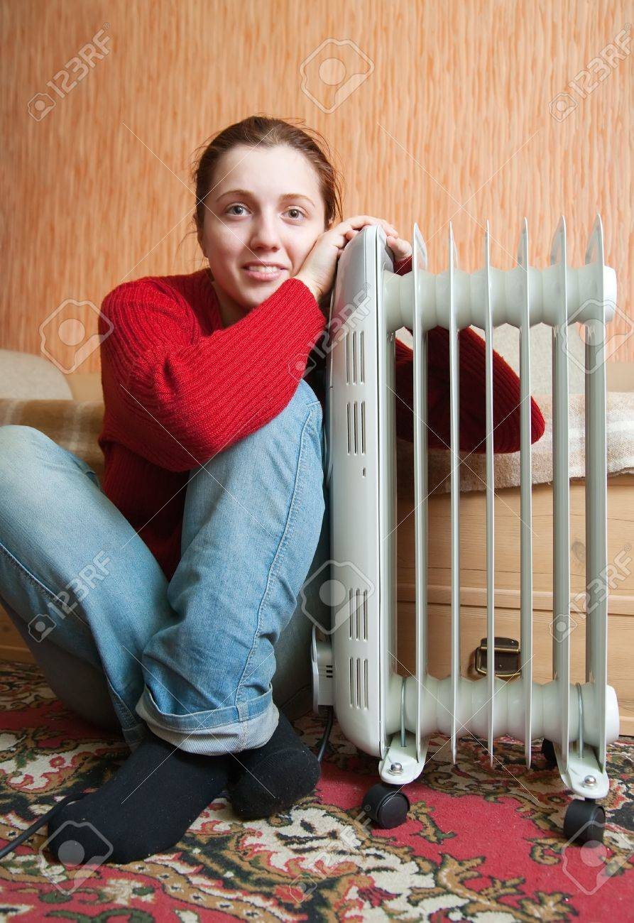 young smiling girl is sitting near oil heater Stock Photo - 7619388