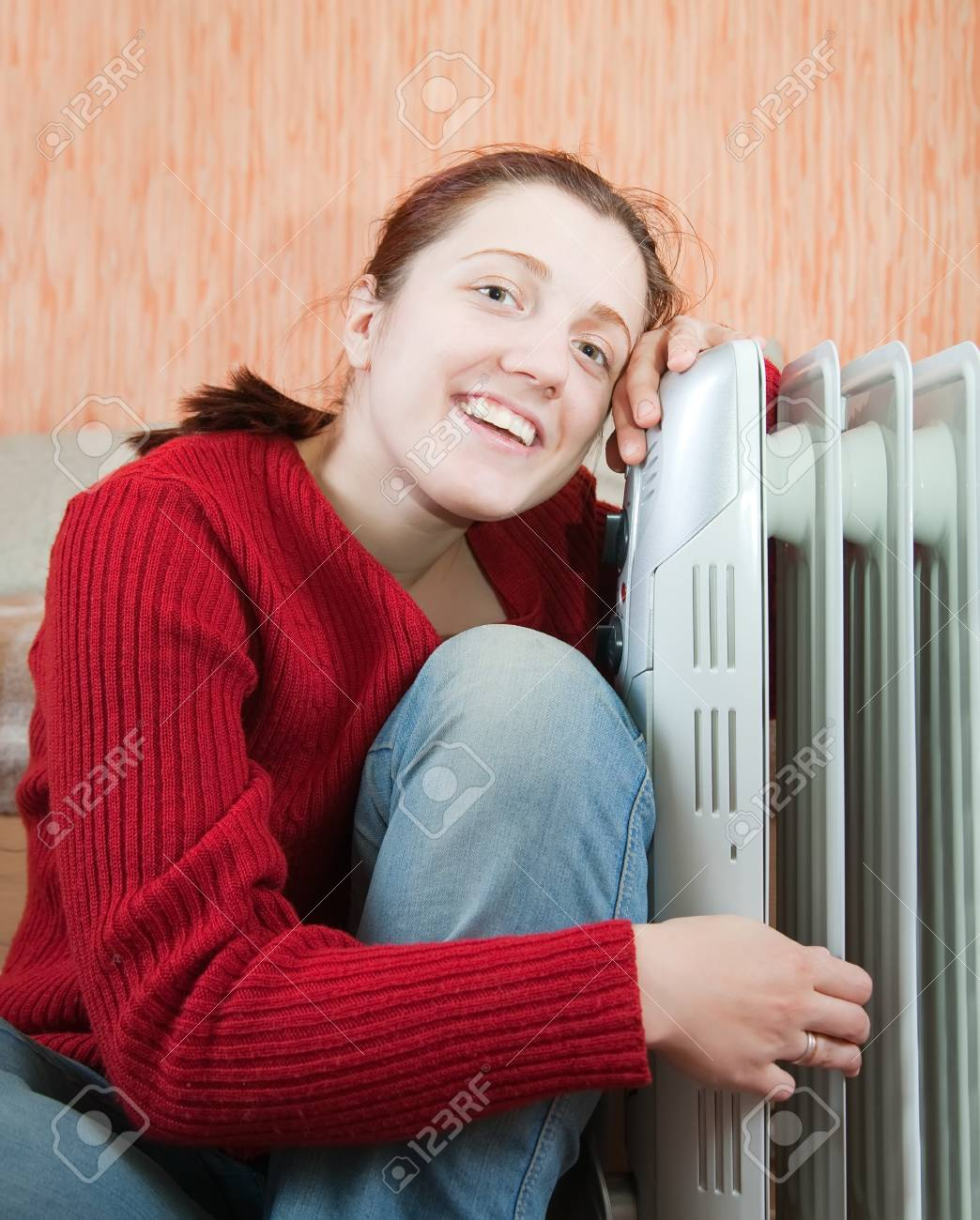 young smiling girl is sitting near oil heater Stock Photo - 7619395