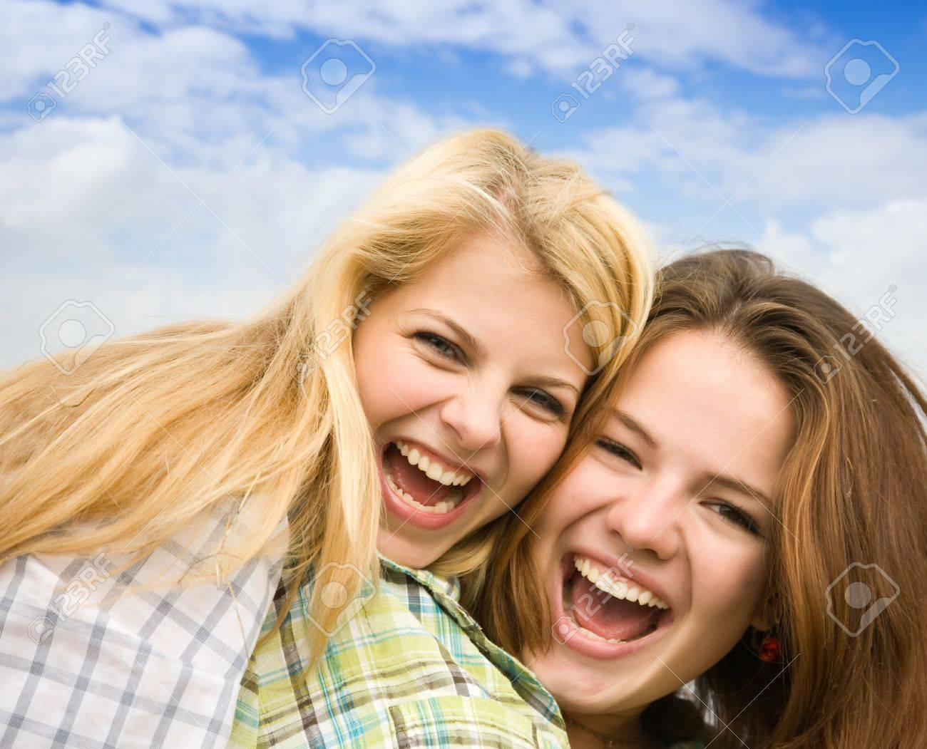 Two happy girls together against cloudy sky Stock Photo - 7777658