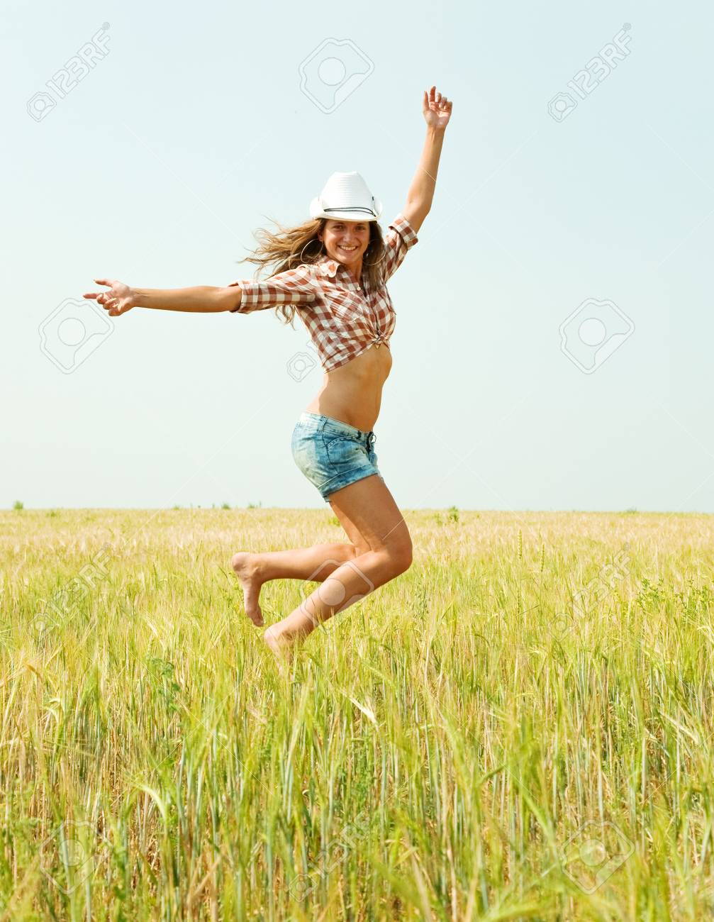 Jumping girl  at cereals field in summer Stock Photo - 7941615