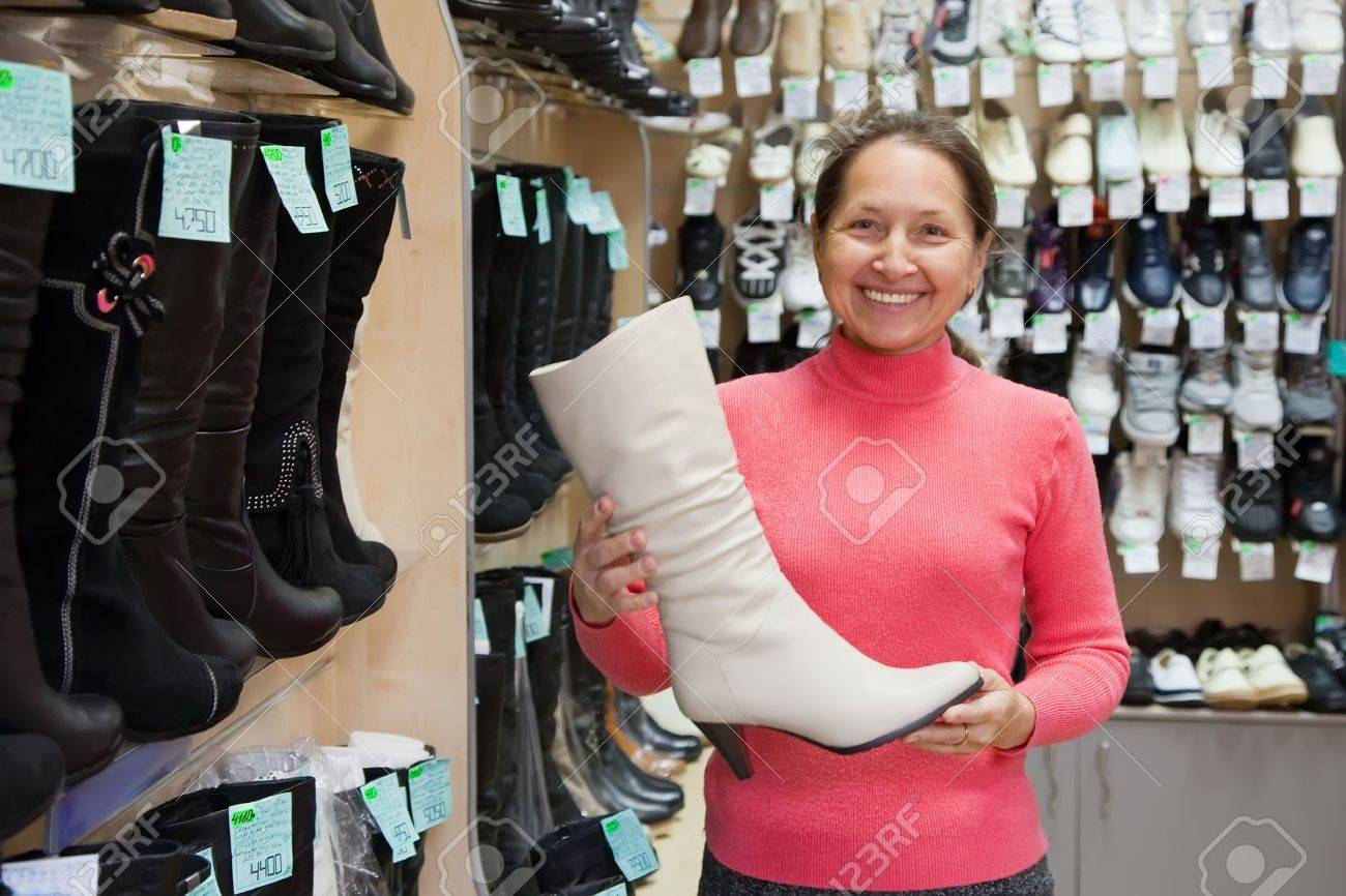 Mature woman chooses wintry shoes at shoes shop Stock Photo - 8071863