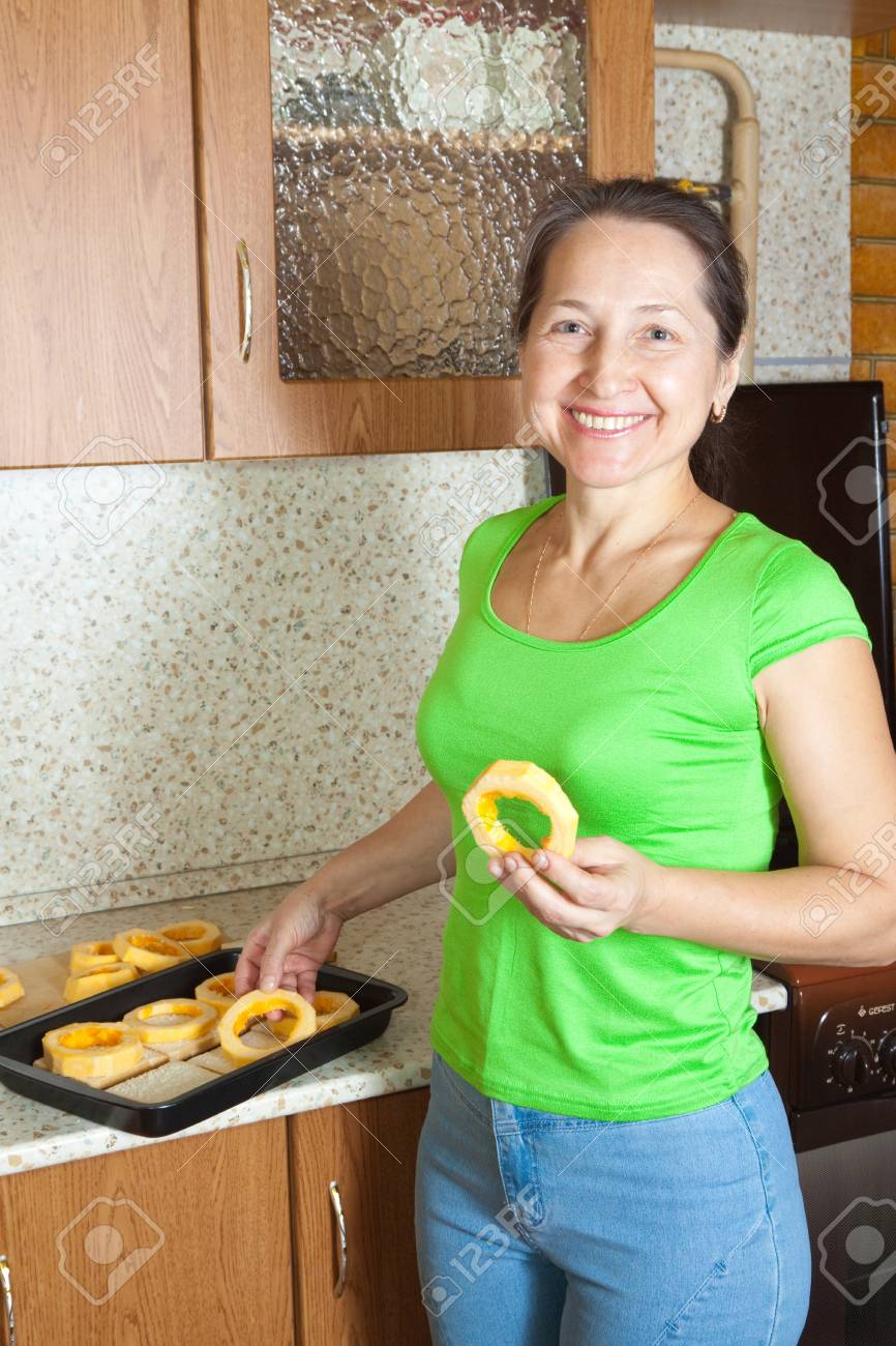 Woman puts vegetable marrow rings into roasting pan.