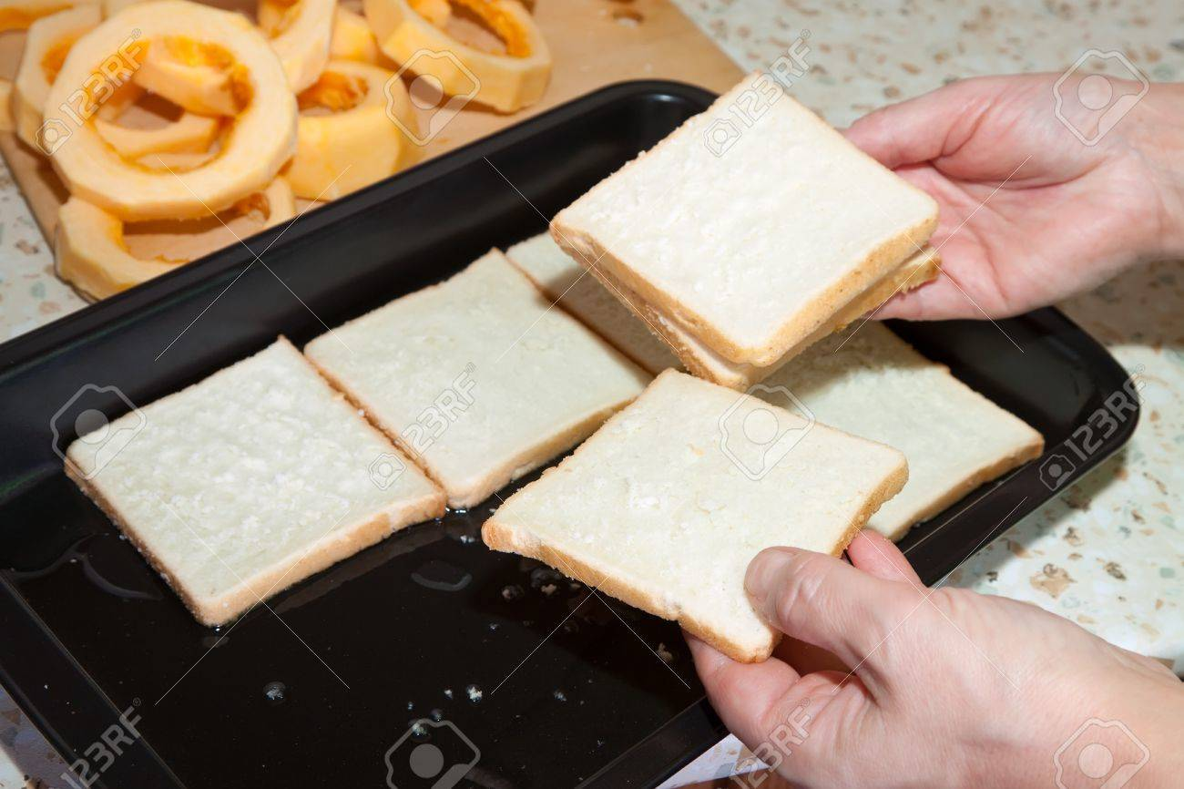 Cook puts toast bread into roasting pan.See in series stages of cooking of stuffed vegetable marrow Stock Photo - 8273643