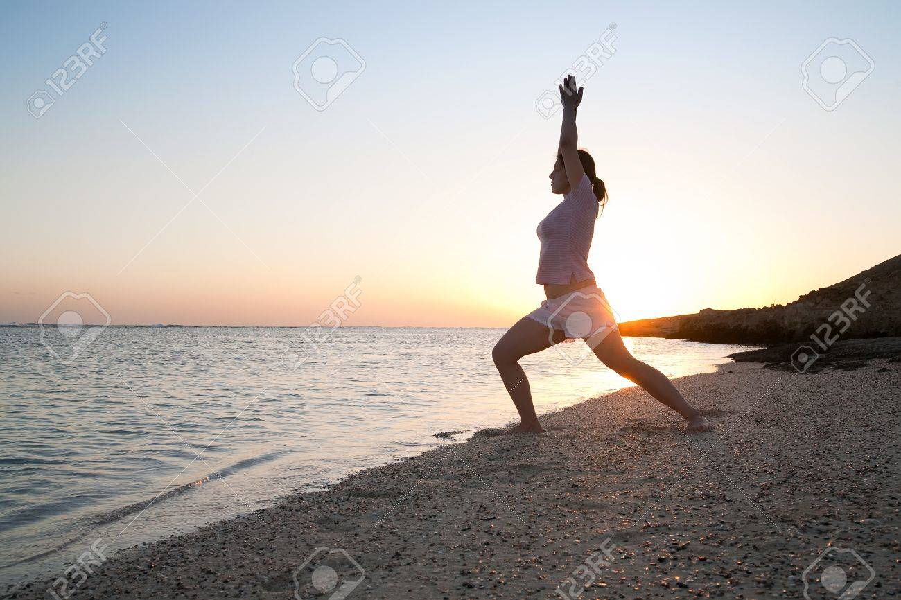 Beautiful young girl practicing yoga  against sunrise Stock Photo - 8333965