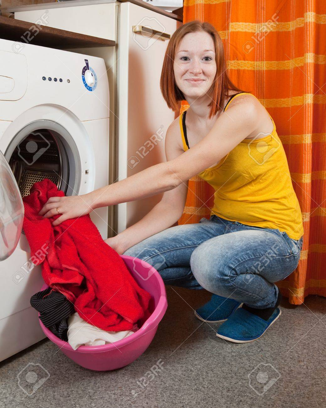 woman putting clothes into washing machine and looking at camera Stock Photo - 8769705