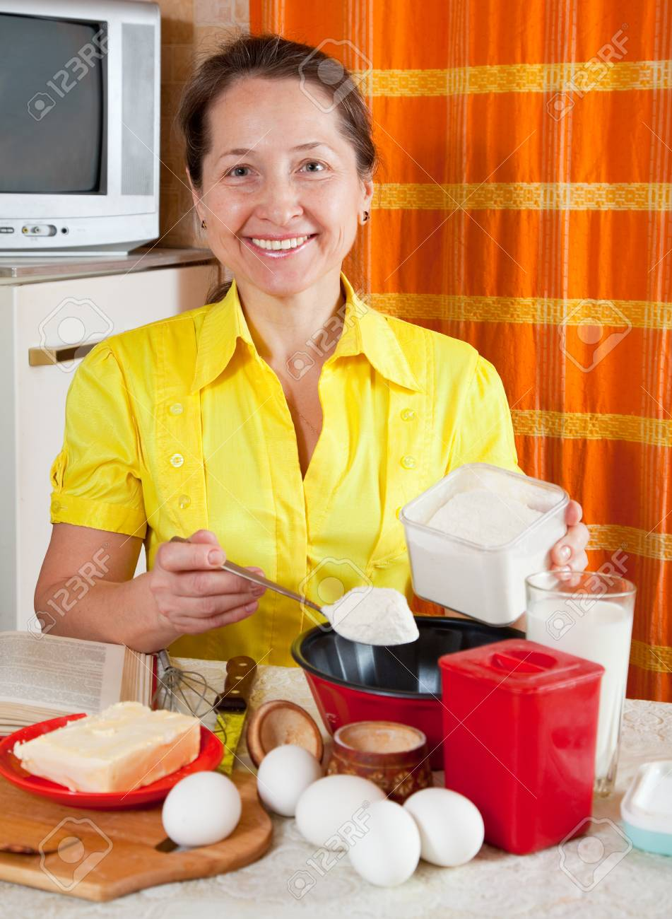 Joyful woman making dough in the kitchen at home Stock Photo - 8769969