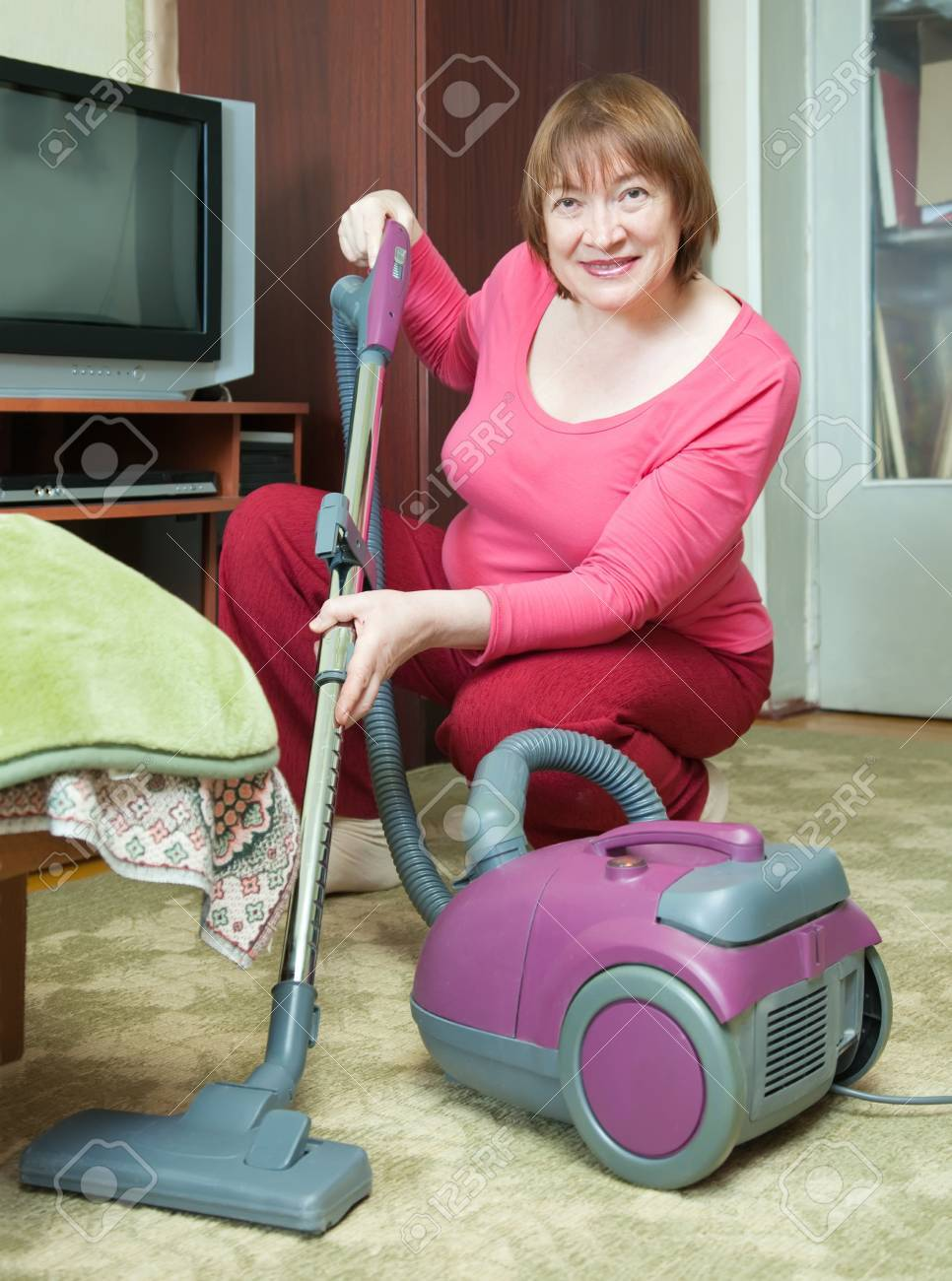 Woman cleaning with vacuum cleaner in living room Stock Photo - 9109479