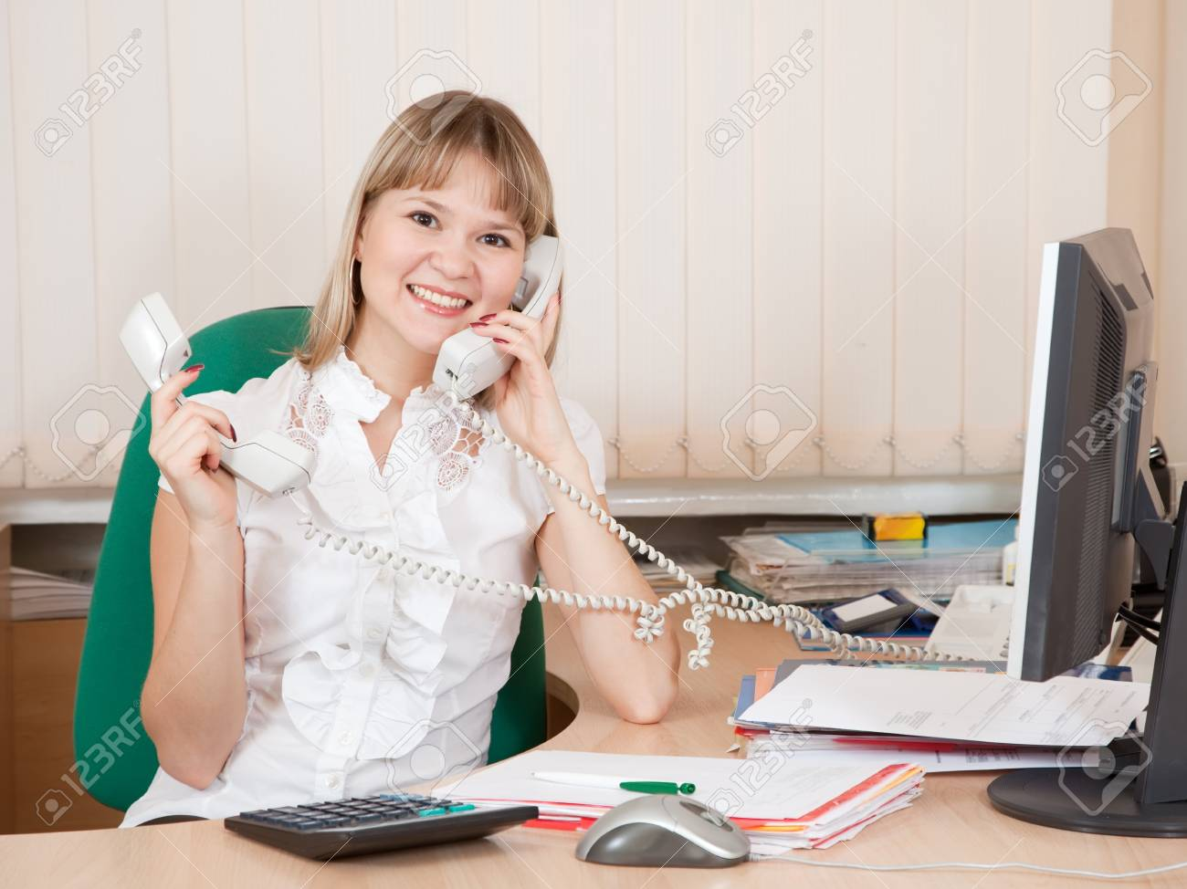 female  manager speaking by two phone in office Stock Photo - 9161528