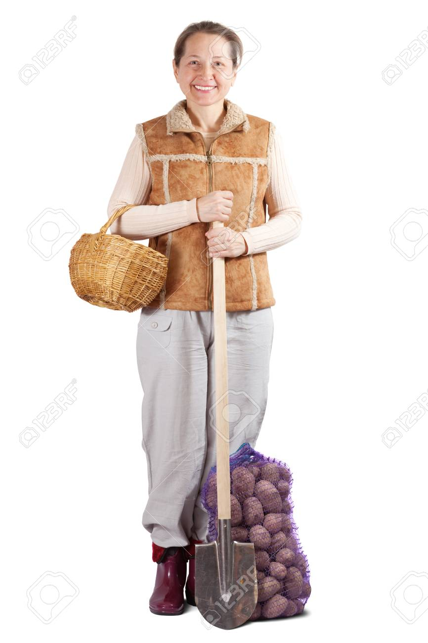 Happy pastoral  woman  with spade and harvested potatoes over white Stock Photo - 9330439