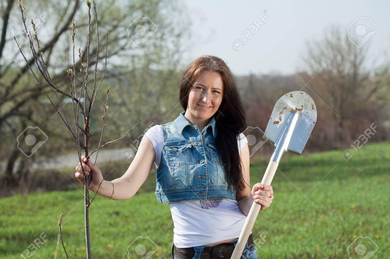 Female gardener planting tree outdoor in spring Stock Photo - 9490353