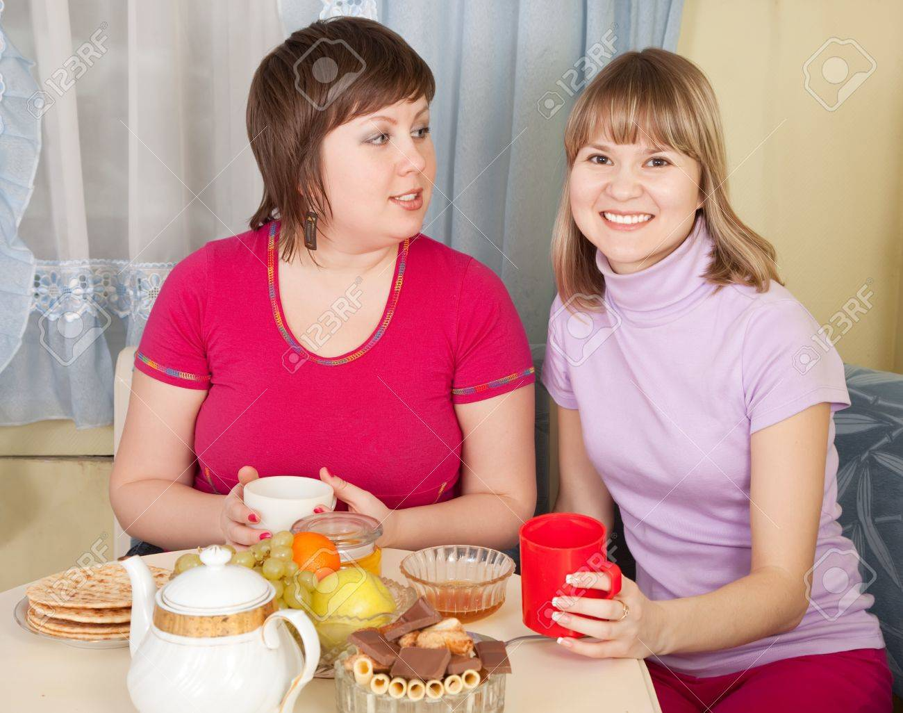 portrait of two girls  drinking tea and gossiping in home Stock Photo - 9854152