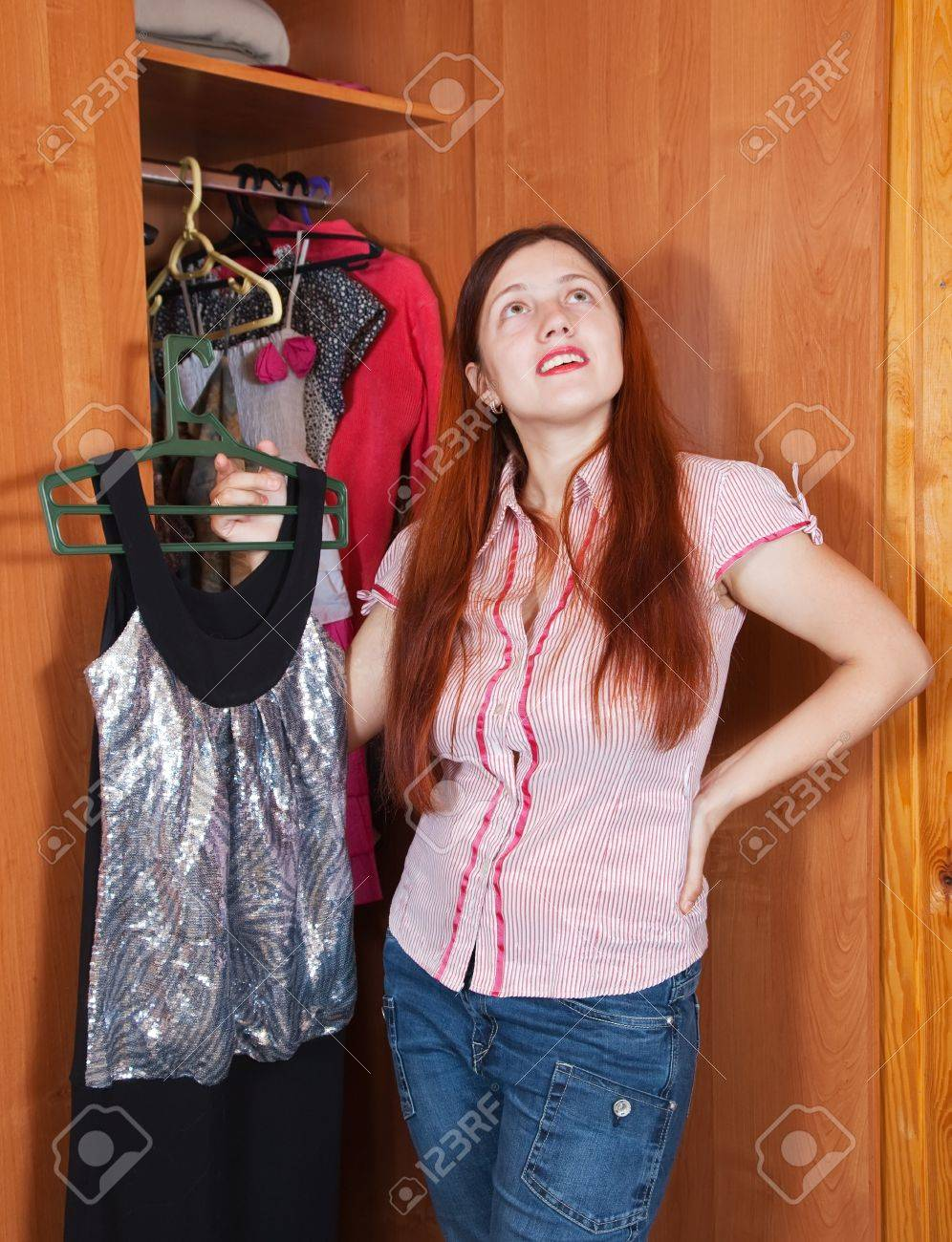 Young woman standing at wardrobe. She thinking what get dressed. Stock Photo - 9854681