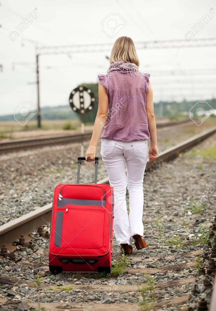Rear View Of Woman With Luggage Walking On Rail Road Stock Photo ...
