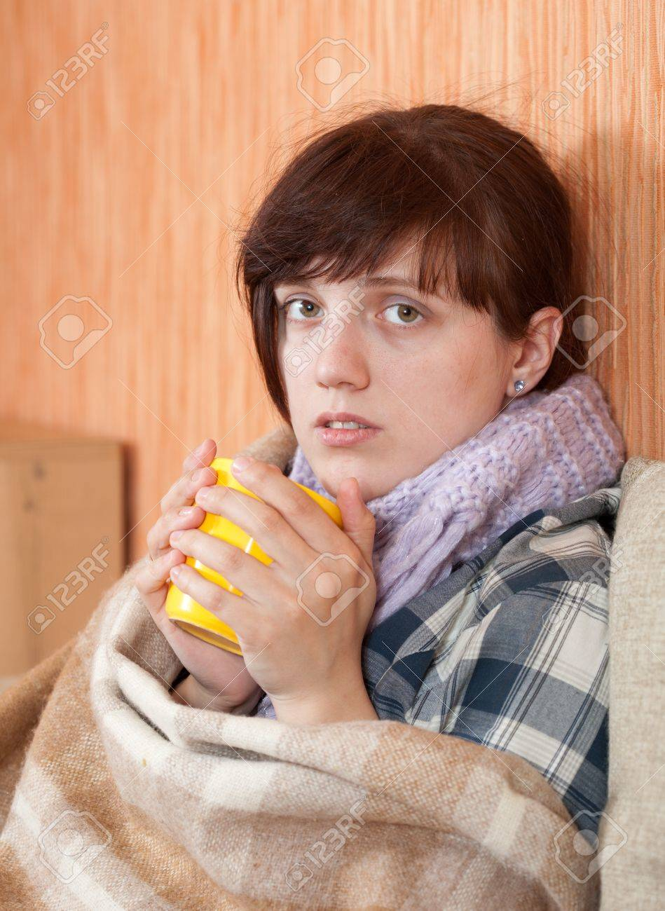 Young illness woman drinking tea in  blanket Stock Photo - 10352353