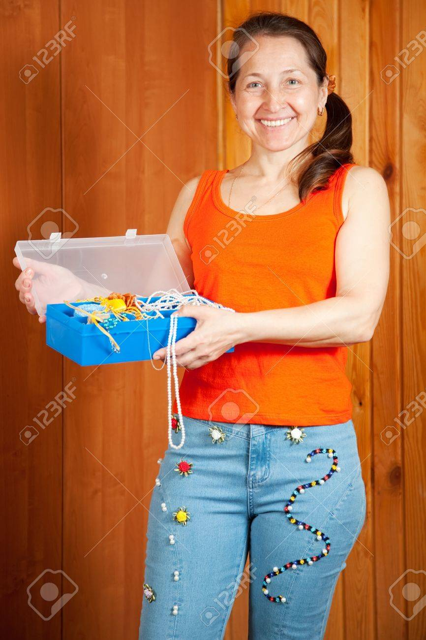 Mature woman  shows a handmade jeans beaded by herself Stock Photo - 10557964