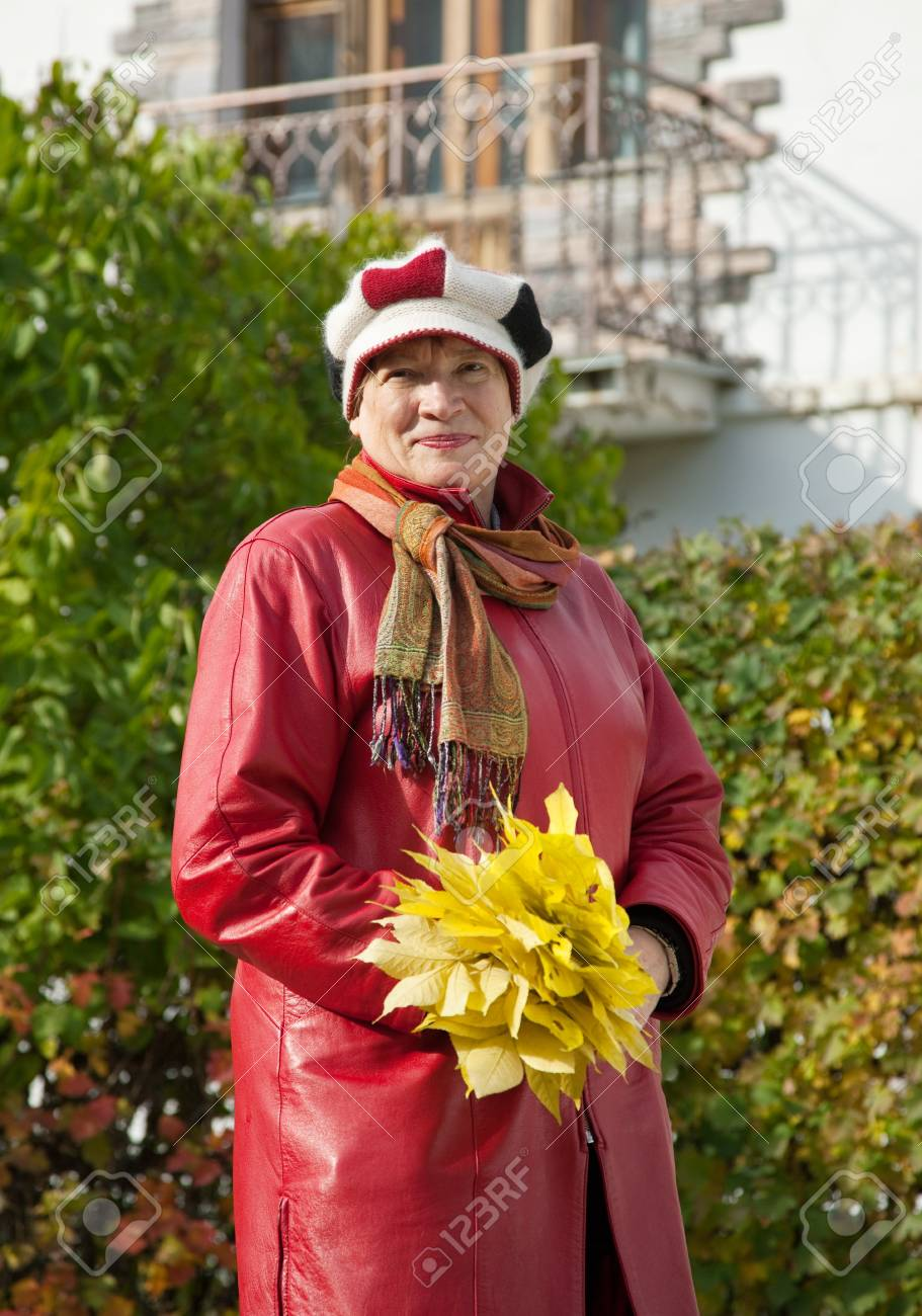 Outdoor portrait of  mature woman with maple posy Stock Photo - 10812754