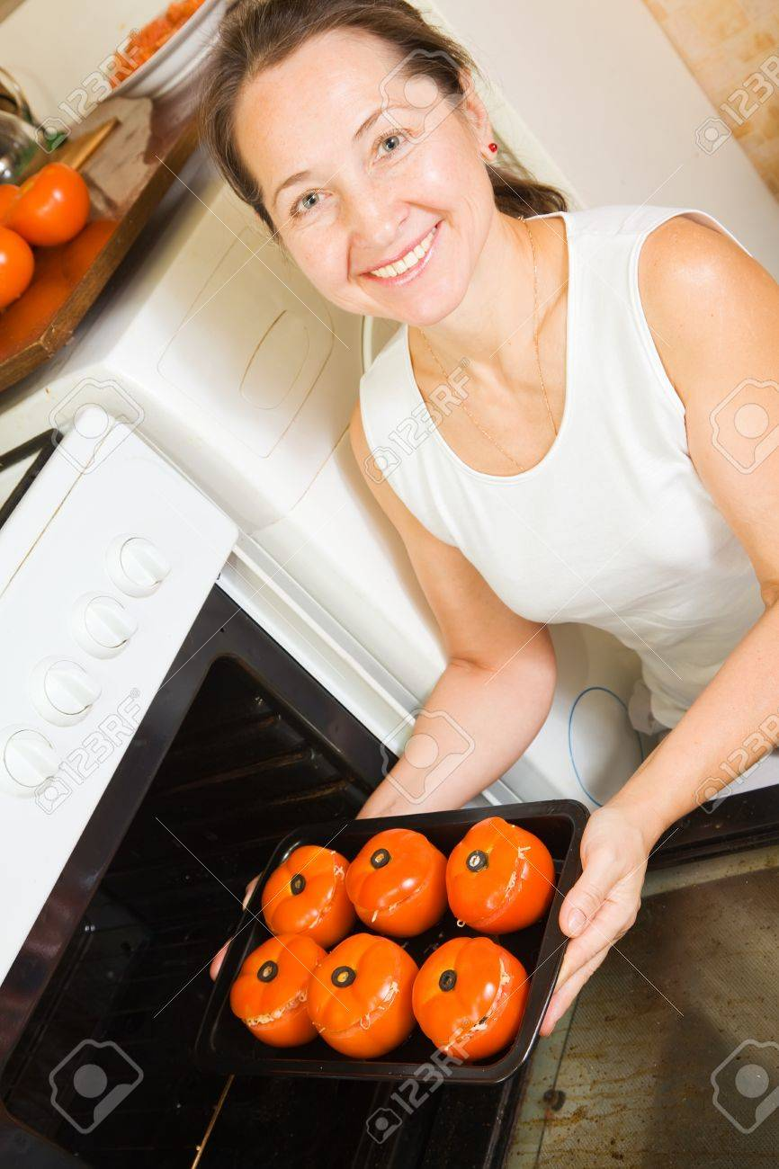 Mature woman roasting stuffed tomato on pan in oven.See in series stages of cooking of farci tomato Stock Photo - 10999006