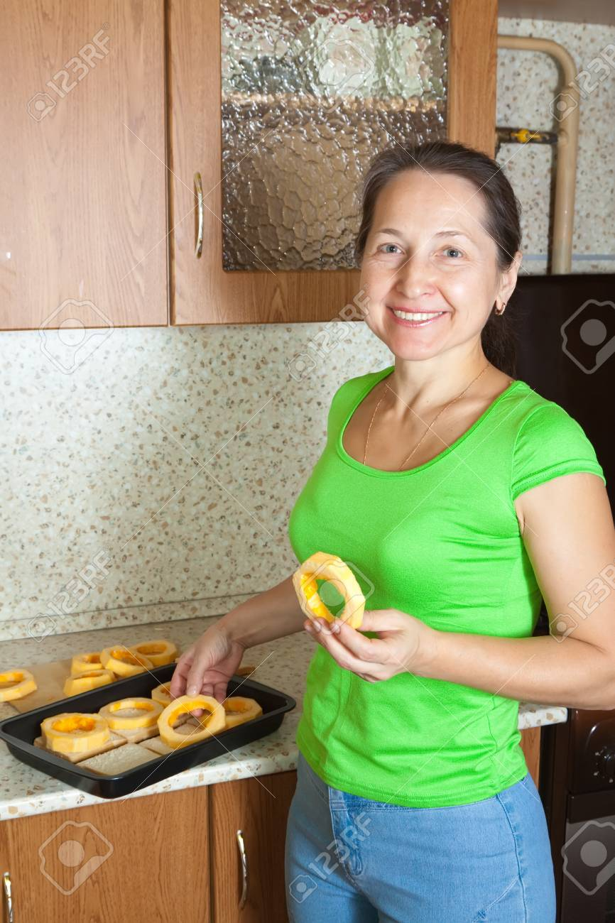 Woman puts vegetable marrow ring into roasting tray.