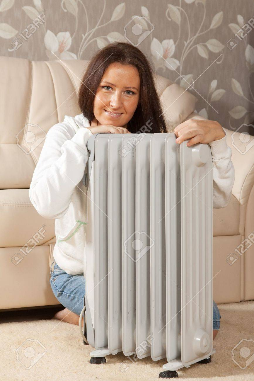 smiling woman   near warm radiator  in home Stock Photo - 11479952