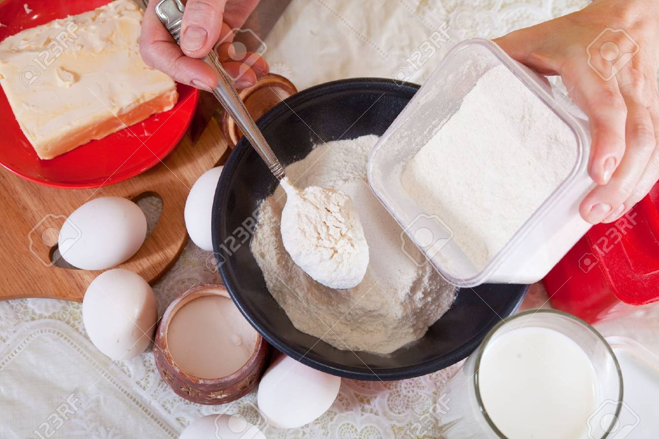 Closeup of cook hands pours  flour in to pan Stock Photo - 11955173