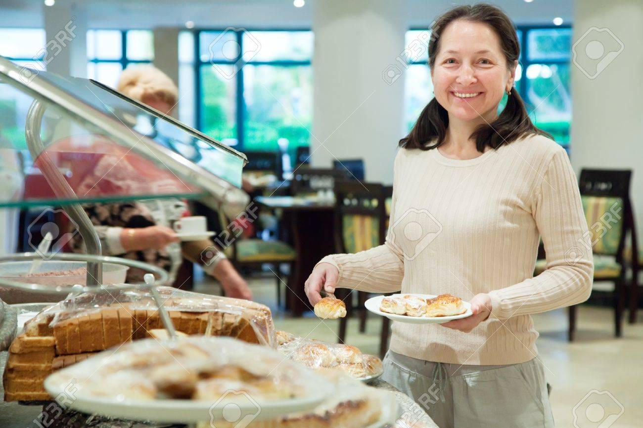 Woman chooses sweet pastry in buffet at hotel Stock Photo - 17203736