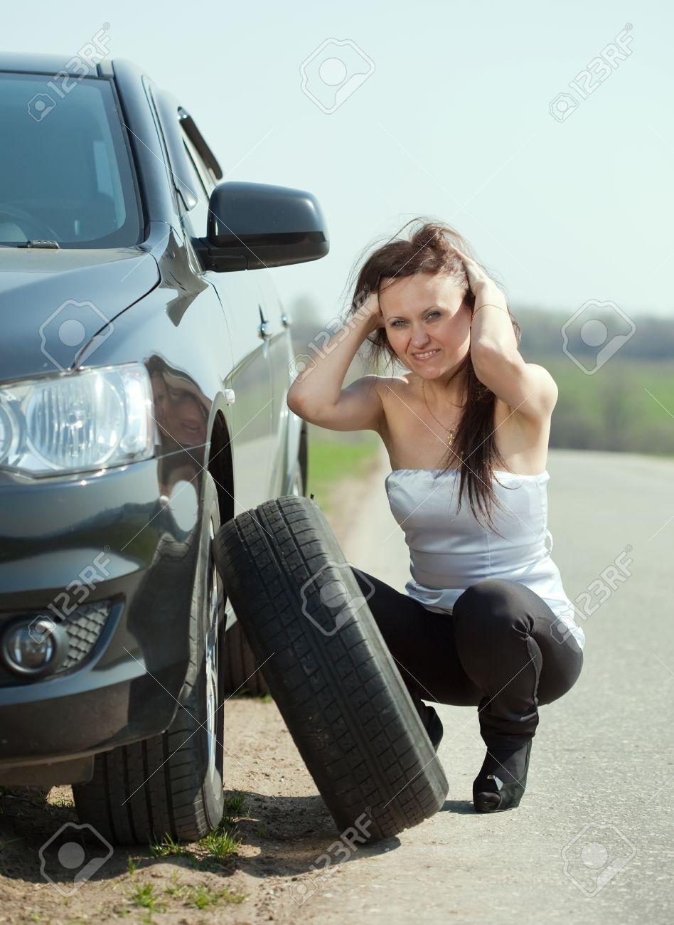 Woman changing car wheel at road Stock Photo - 12289292