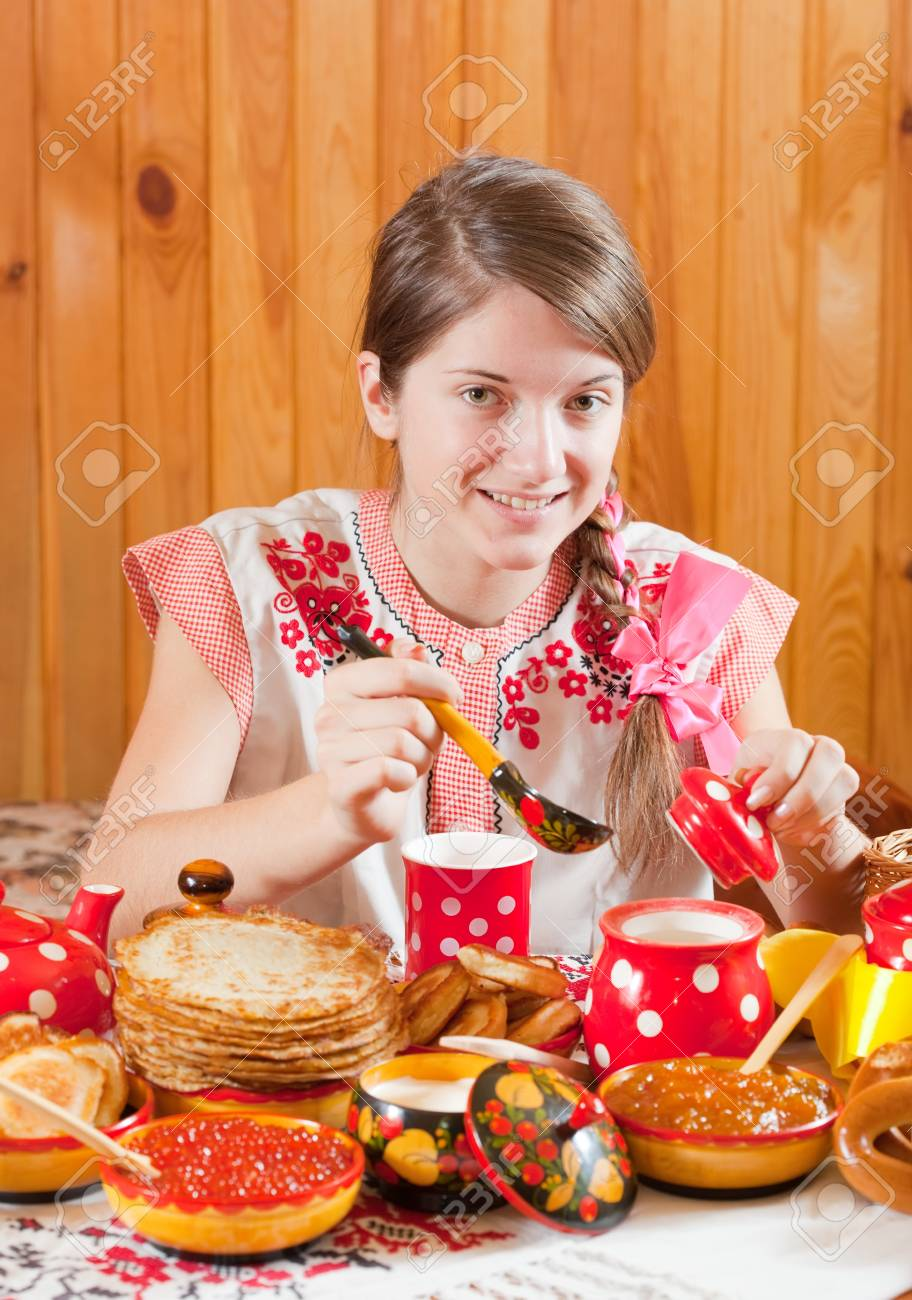 Girl in traditional  clothes eating pancake during  Shrovetide Stock Photo - 12289089