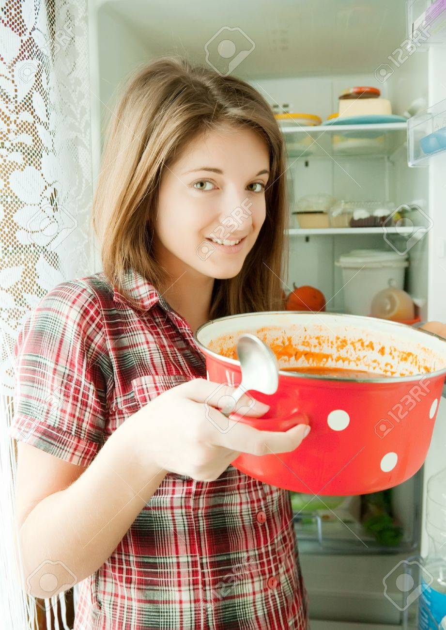 Teenager girl eating  soup from pan near fridge  at home Stock Photo - 12437032