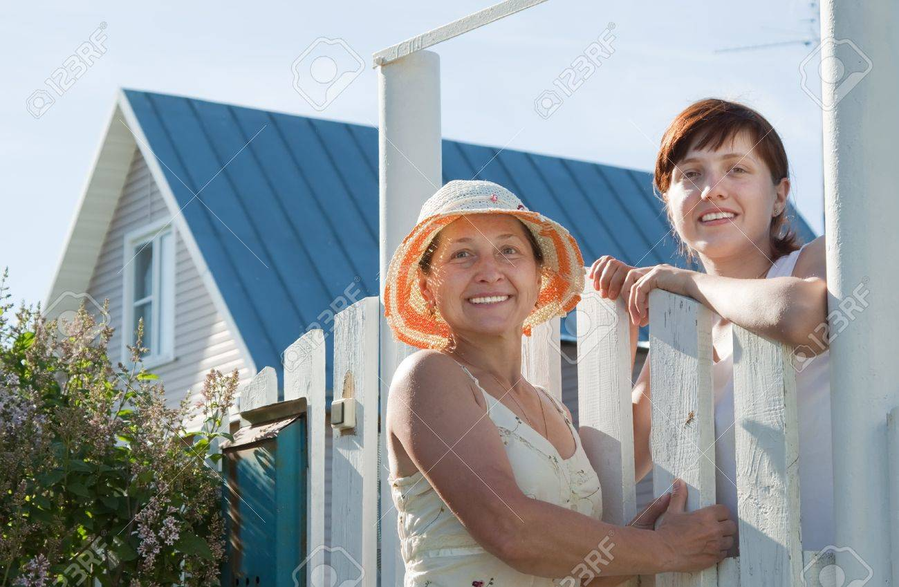Two happy women near fence wicket  in front of home Stock Photo - 12601993