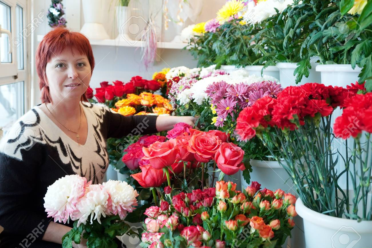 woman in the shop surrounded by different flowers Stock Photo - 12791593