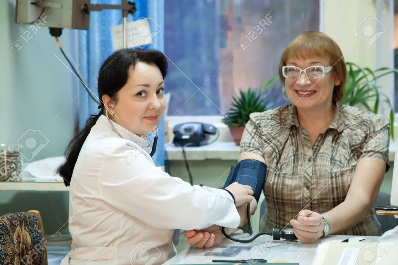 Doctor measuring blood pressure of patient  in clinic Stock Photo - 13119873