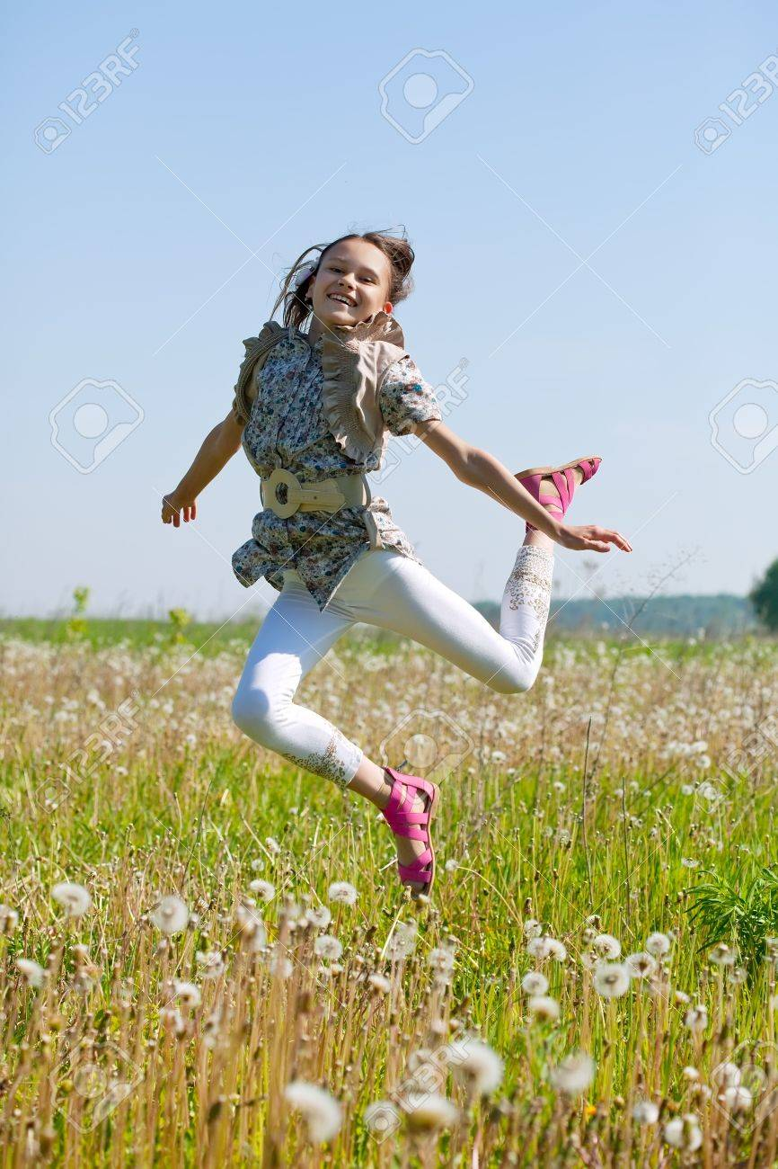 Jumping long-haired teen girl against nature Stock Photo - 13200971