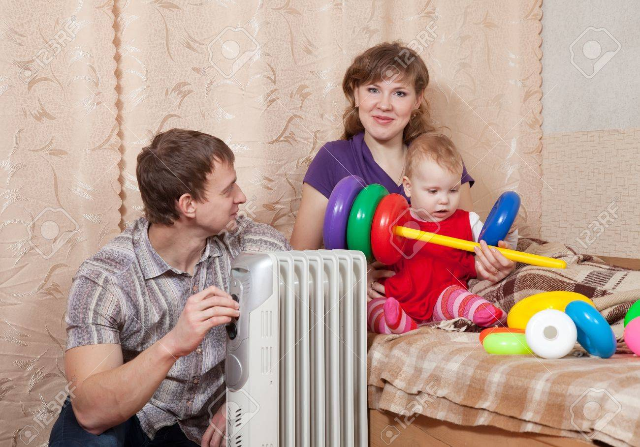 Family  relaxing at home near oil heater Stock Photo - 13394783
