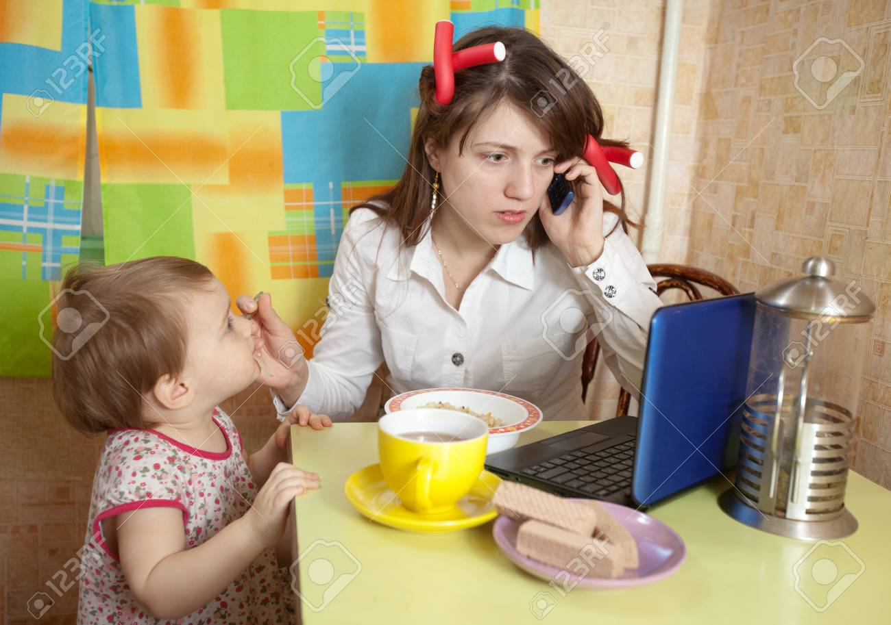 Mother feeding baby and  using  latop at kitchen in morning Stock Photo - 13779112