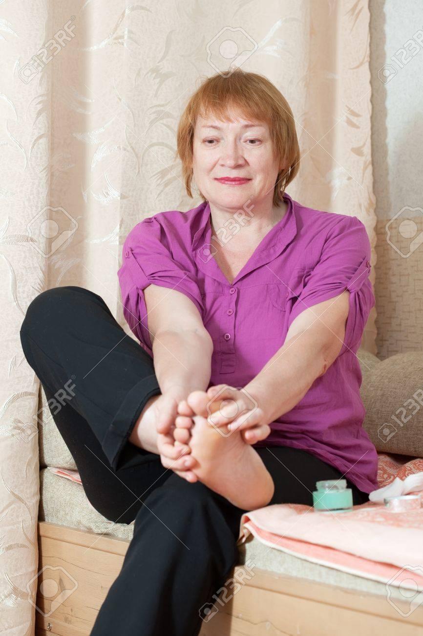 Mature woman looks at her toenails Stock Photo - 14024776