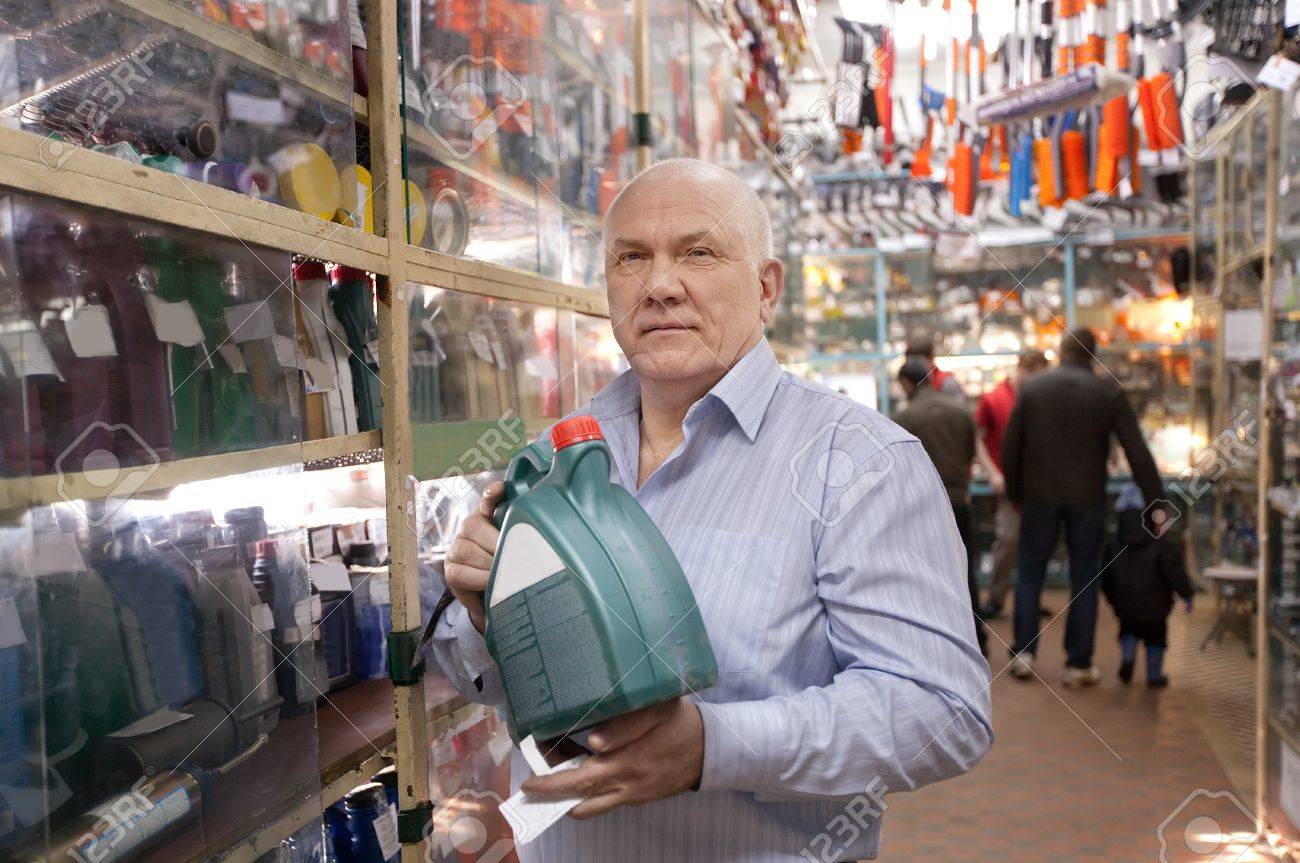 Mature man holds  motor oil in  auto  parts store Stock Photo - 14531000