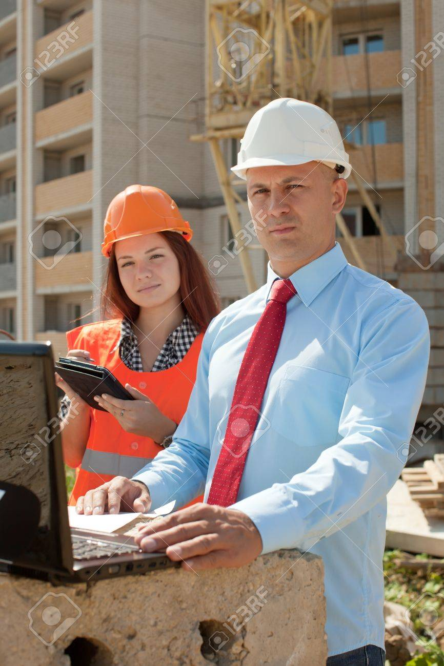 two builders wearing protective helmet works on the building site Stock Photo - 15044894