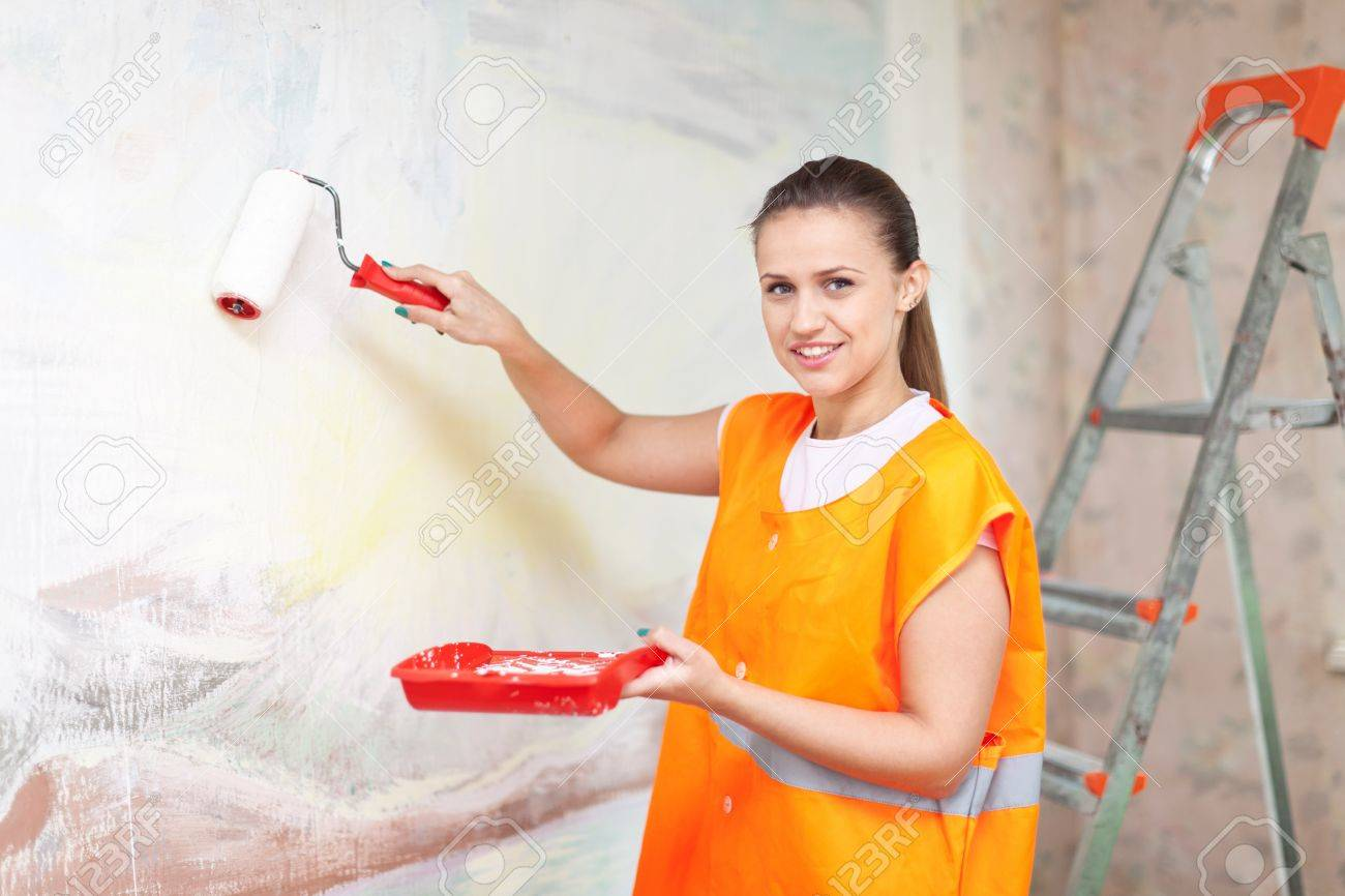 Female housepainter paints wall with roller Stock Photo - 15401970
