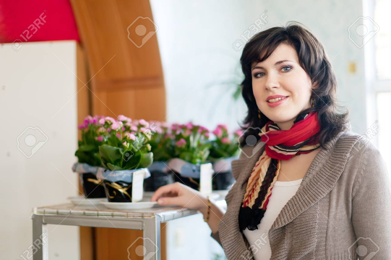 woman in flower shop near the shelves with flower pots Stock Photo - 15443021